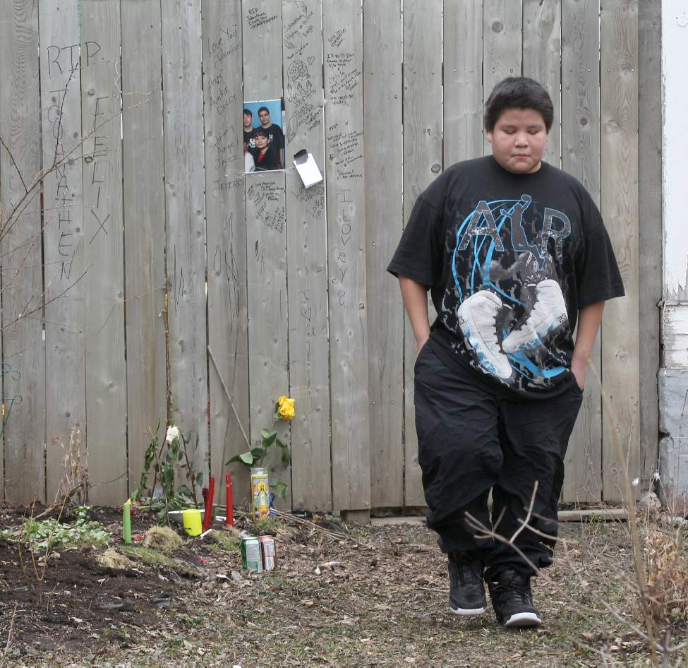 A young boy cries after visiting the memorial in the 200 block of Balmoral St to pay tribute to murder victim Johnathen James Felix. This area is where police located his body Saturday.  (JOE BRYKSA / WINNIPEG FREE PRESS)