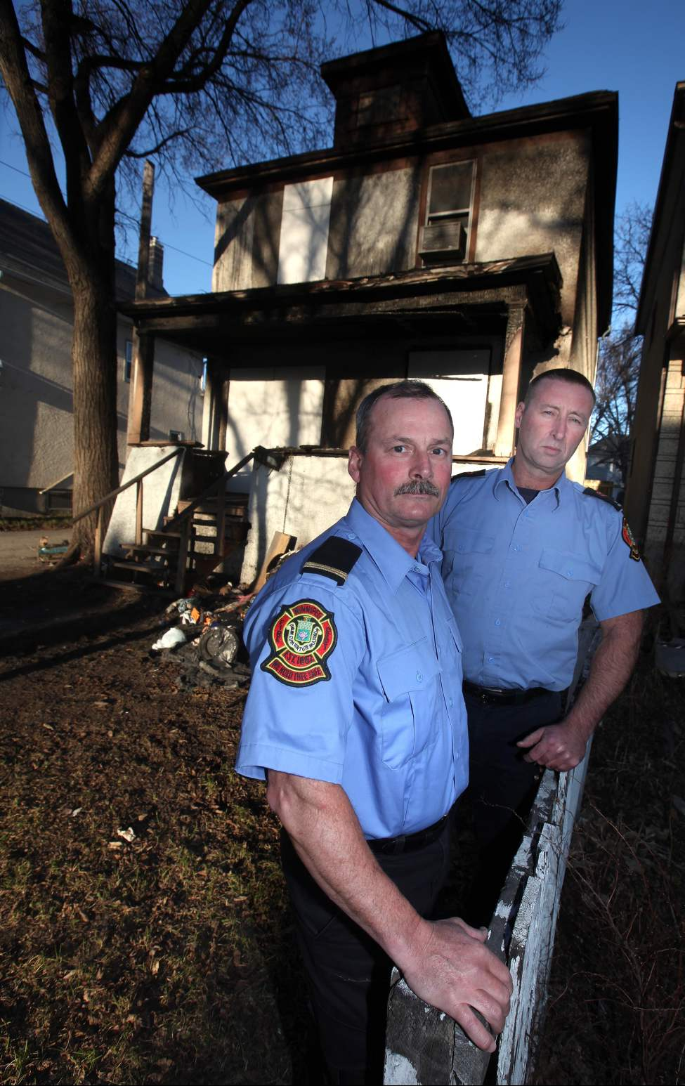Veteran city firefighters Lt Gerry Nikkel (left) and Ken Proulx pose in front of a Home Street house where the pair helped the occupants to safety through a wall of fire Monday morning. April 4, 2012.  