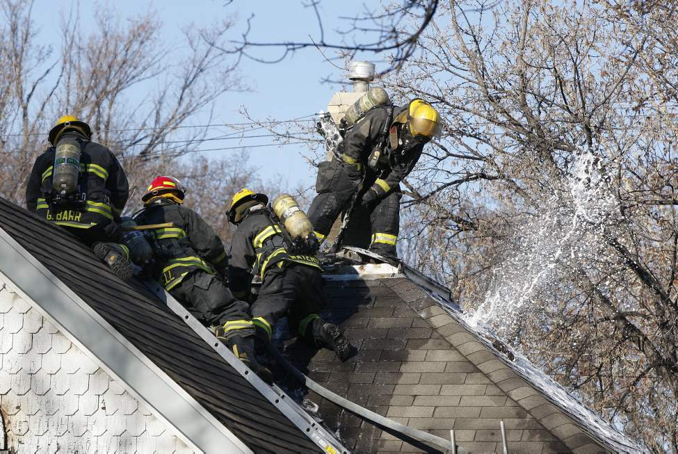 House fire 502 Langside Street. Firefighters begin to open up the roof of the older one story home  as  hose spraying foam shoots through roof. April 4, 2012.