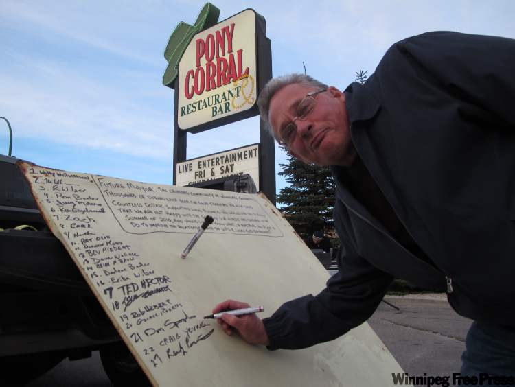 Craig Young from Gull Lake signs the hood of a 1958 Chevrolet.
