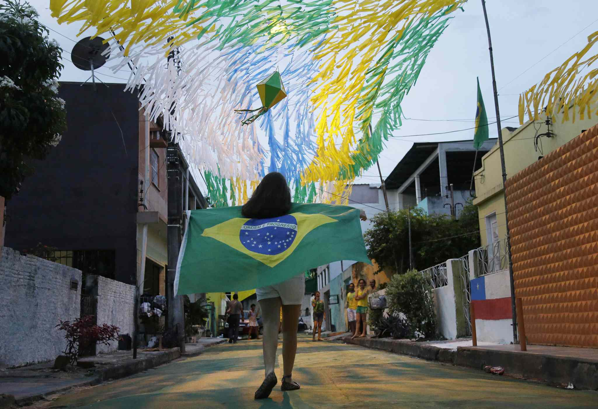 A girl walks down an alleyway holding a Brazilian flag after the country's winning opening match over Croatia during the 2014 soccer World Cup in Manaus, Brazil.