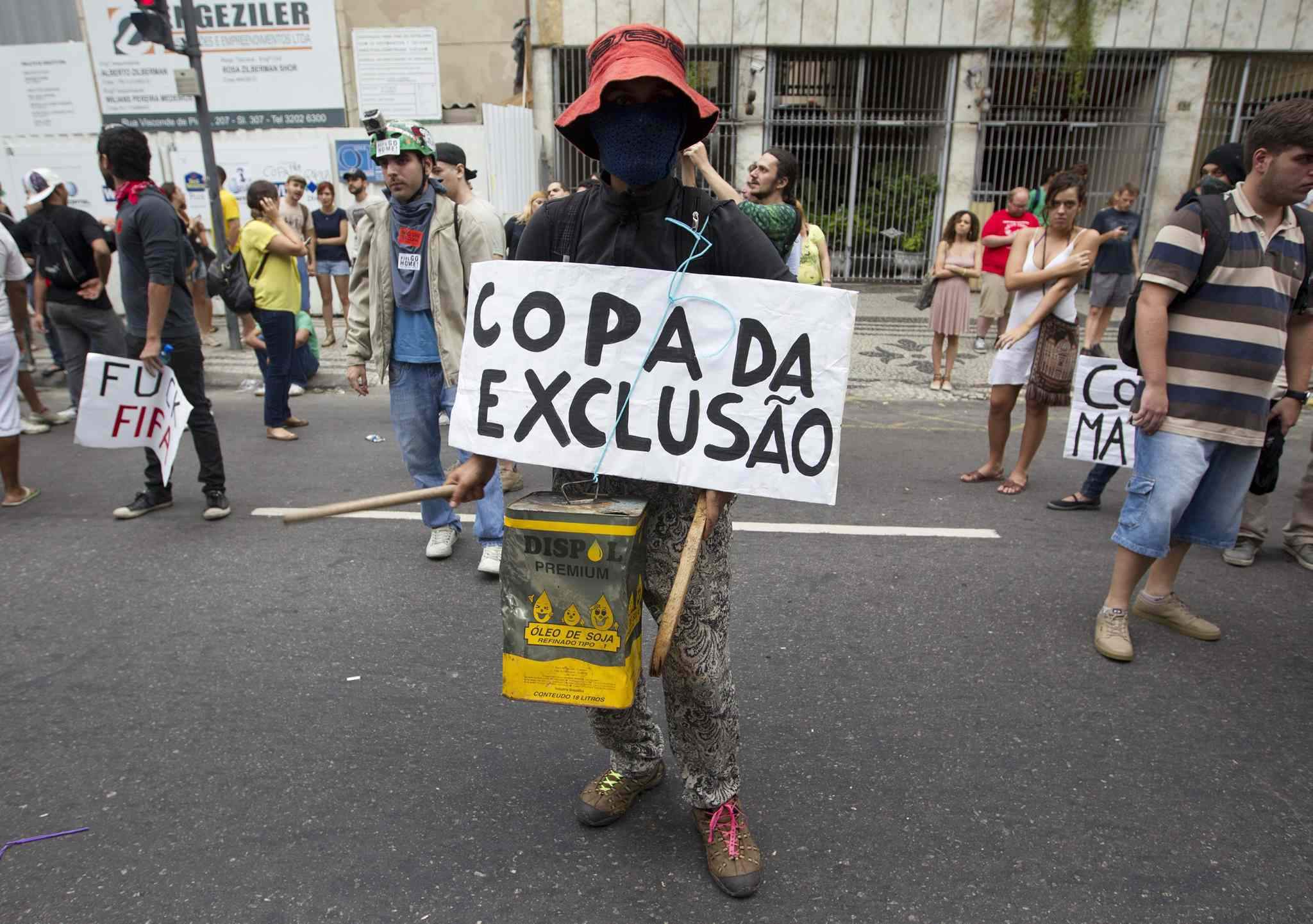 A demonstrator protests with a sing that reads in Portuguese,