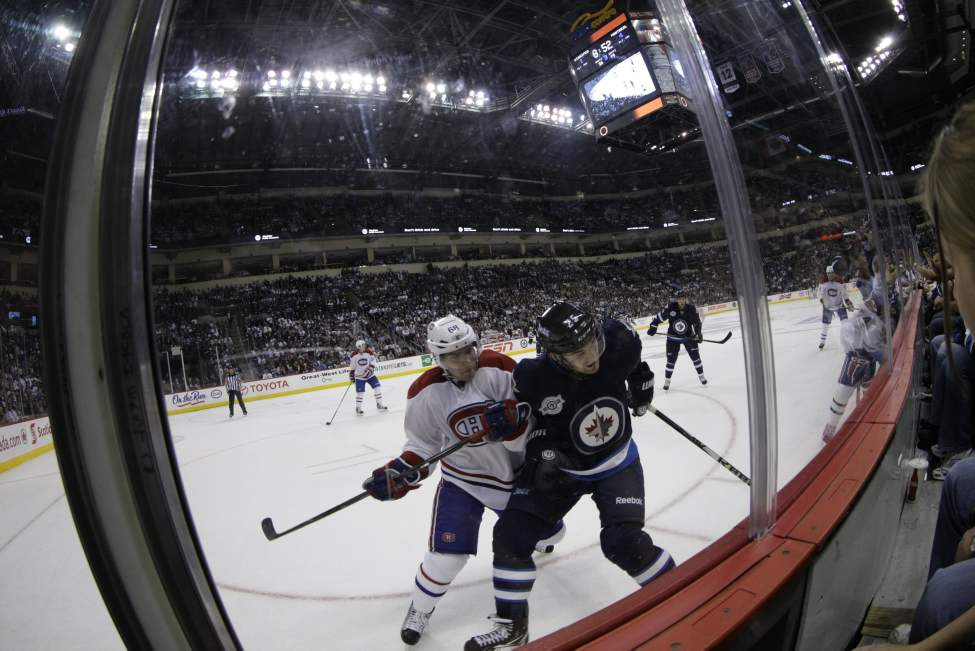 Brett MacLean battles with Yannick Weber during third-period action. (Trevor Hagan / Winnipeg Free Press)