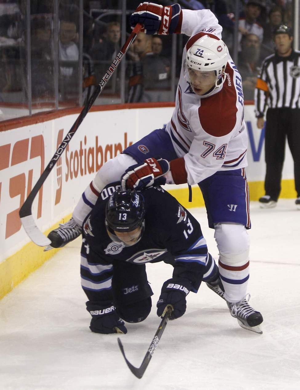 Canadien Alexei Emelin jumps over downed Jet Kyle Wellwood behind the Montreal net during second-period action. (Trevor Hagan / Winnipeg Free Press)