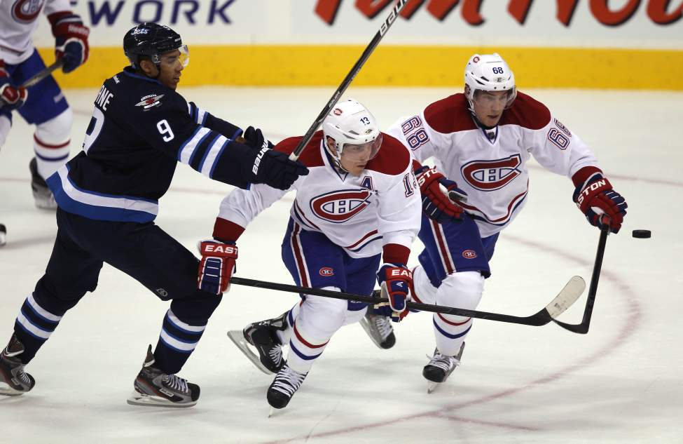 Evander Kane chases the puck against Canadiens Michael Cammalleri and Yannick Weber during first-period action. (Joe Bryksa / Winnipeg Free Press)