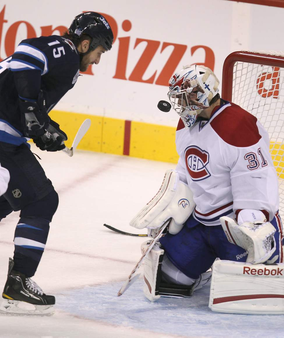 Montreal Canadians goaltender Carey Price keeps his eyes on the puck as Winnipeg Jets Tanner Glass storms the net during third period. (Joe Bryksa / Winnipeg Free Press)