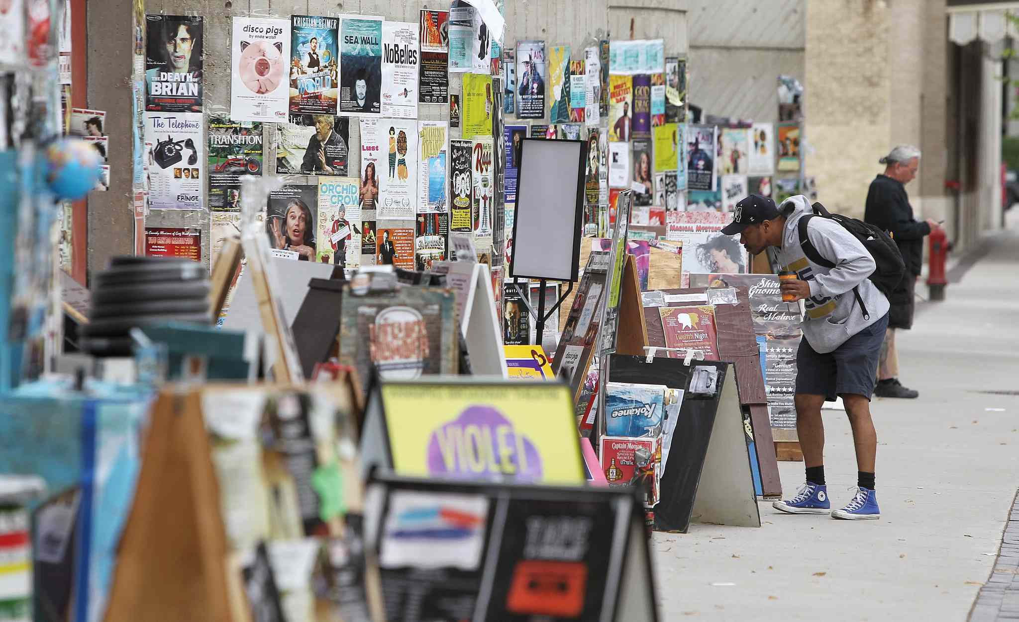 A man checks out Fringe Festival signs while walking along Market Avenue towards the Royal MTC. (Mike Deal / Winnipeg Free Press)