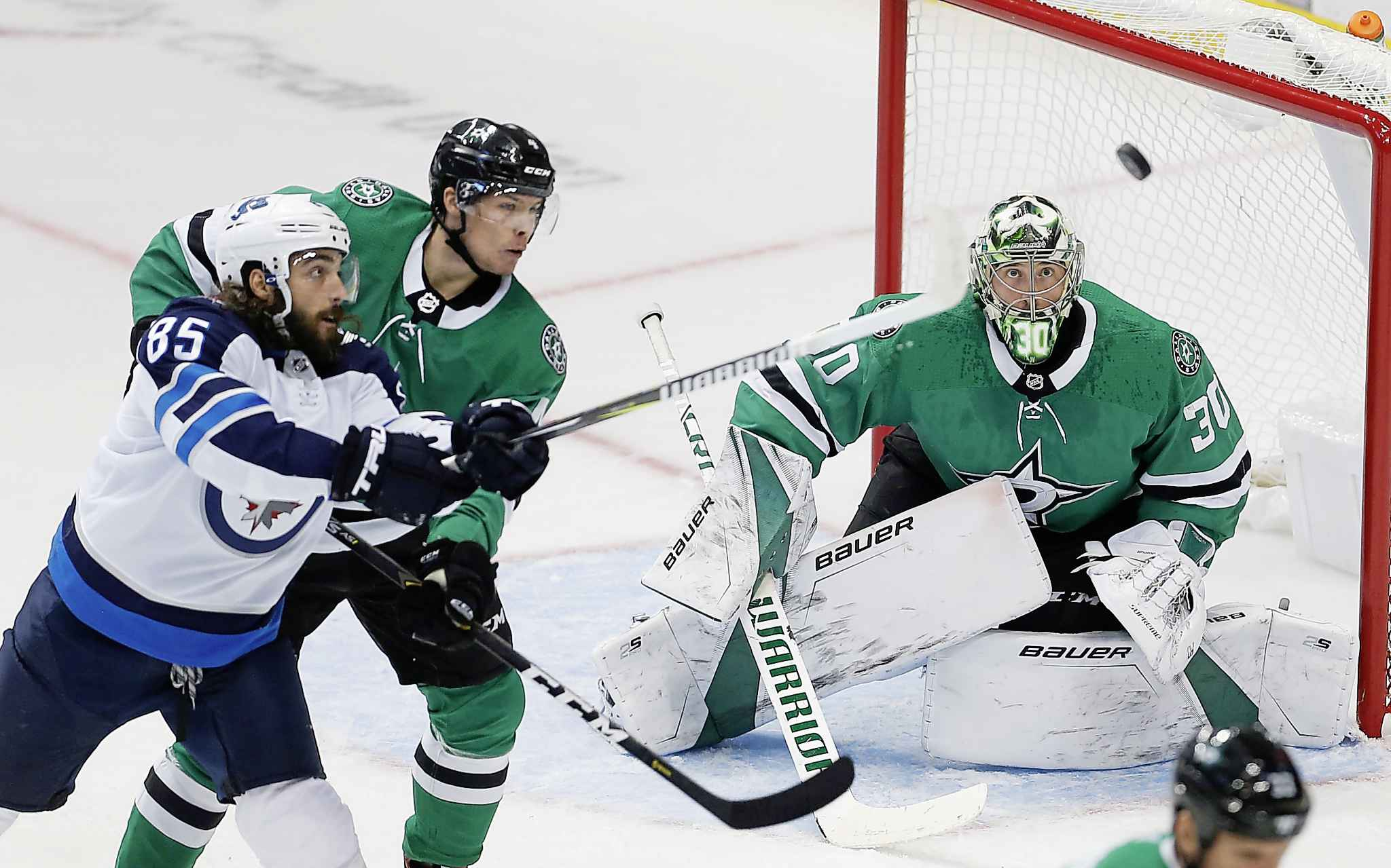 Winnipeg Jets forward Mathieu Perreault (85) reaches for an airborne puck as Dallas Stars defenseman Miro Heiskanen (4) goaltender Ben Bishop (30) defend during the first period of an NHL hockey game, Saturday, Oct. 6, 2018, in Dallas. (AP Photo/Brandon Wade)