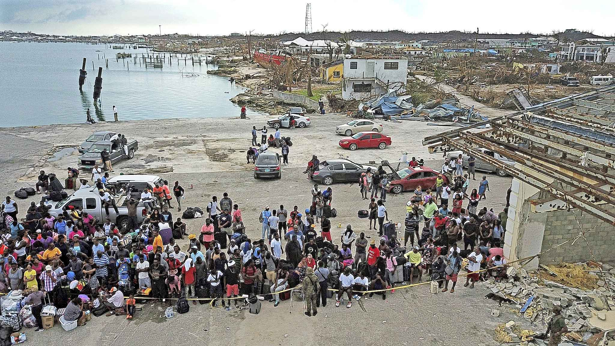 Evacuees gather at Marsh Harbour Port in Abaco, Bahamas, Friday, Sept. 6, 2019. Carrying their meager possessions in duffel bags and shopping carts, hundreds of desperate storm victims gathered at the port in Grand Abaco on Friday in hopes of getting off the hurricane-devastated island, amid signs of rising frustration over the pace of the disaster-relief effort. (Al Diaz/Miami Herald via AP)