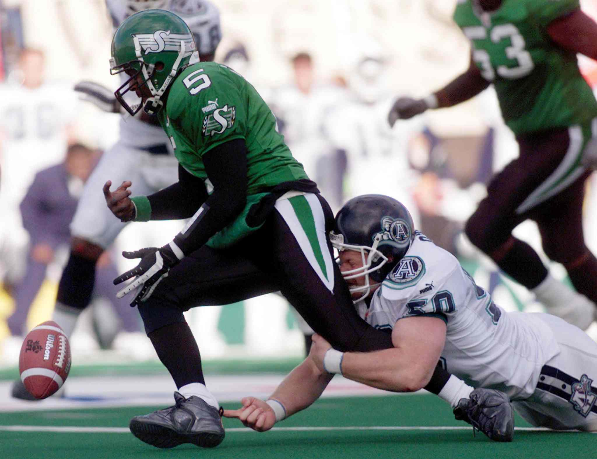 Saskatchewan Roughriders quarterback Kevin Glenn Fumbles the ball during tackle by Toronto Argonaut Mike O'Shea in Regina in 2003. (Geoff Howe / The Canadian Press files)